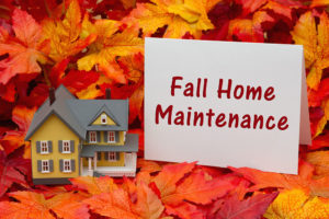 a model home on autumn leaves with a sign stating fall maintenance